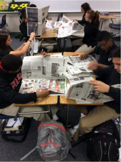 Students using newspapers to